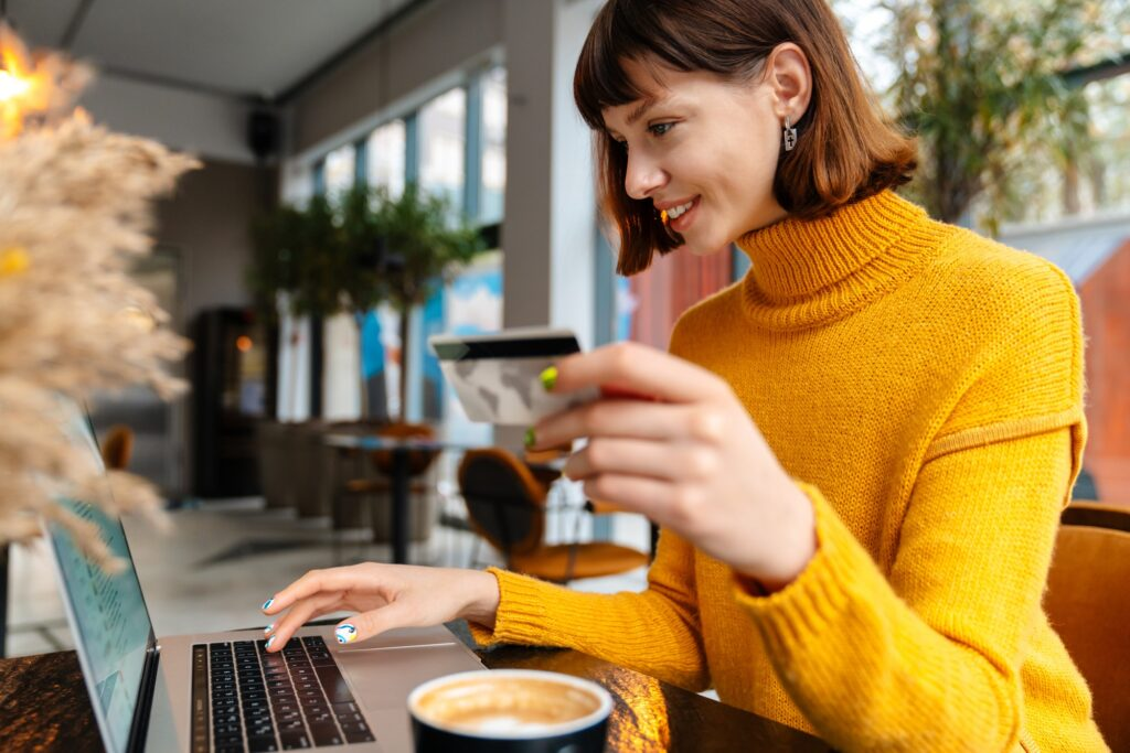 Happy young woman shopping online with credit card