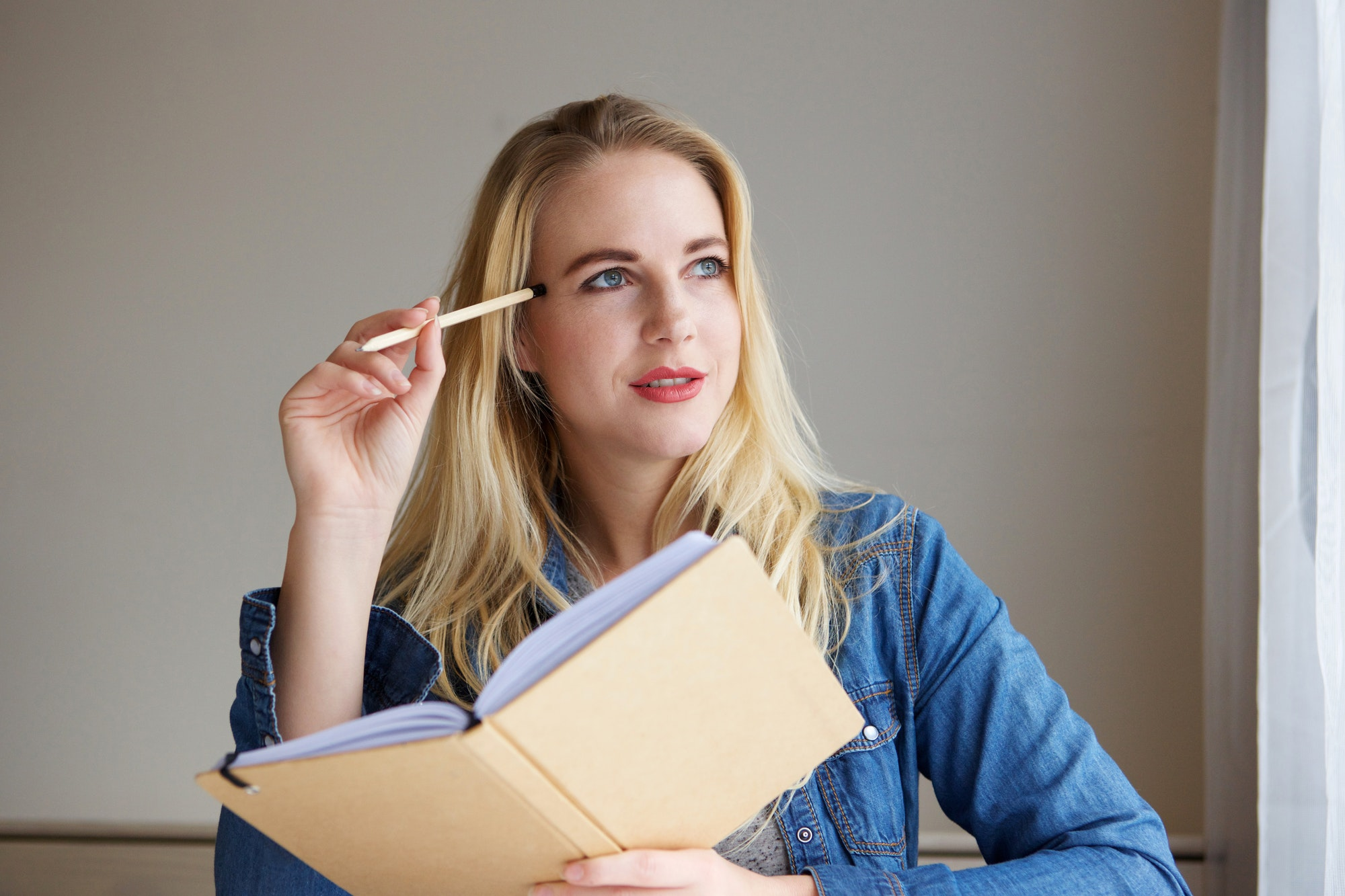 thinking blond woman holding book and pencil and