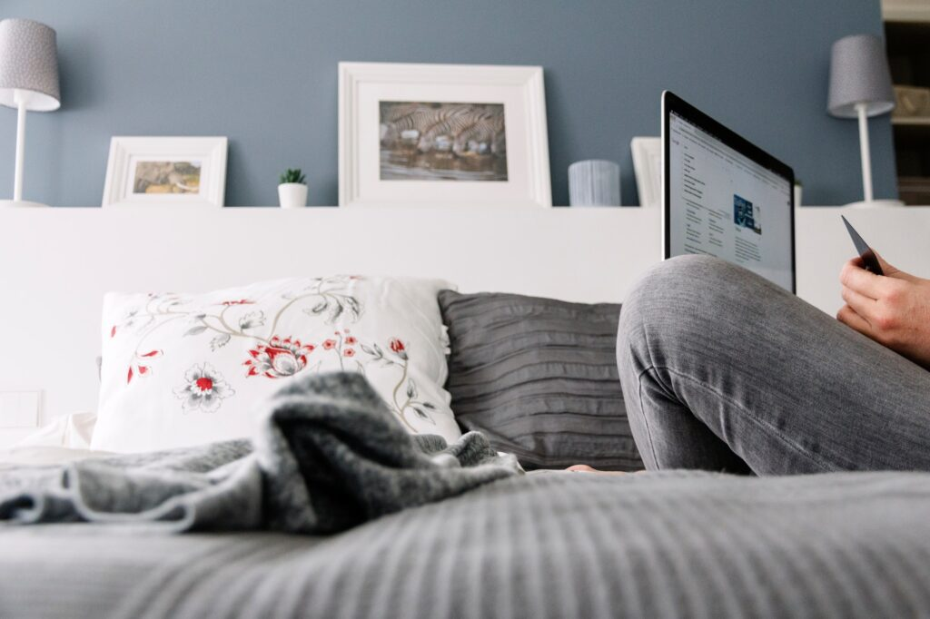 Woman sitting on the bed with a laptop in an apartment. Apartment life, shopping online