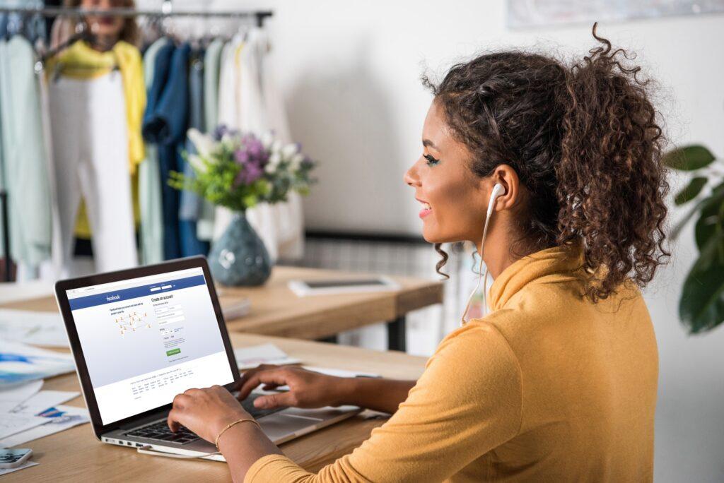 young happy african american woman in earphones using laptop with facebook website