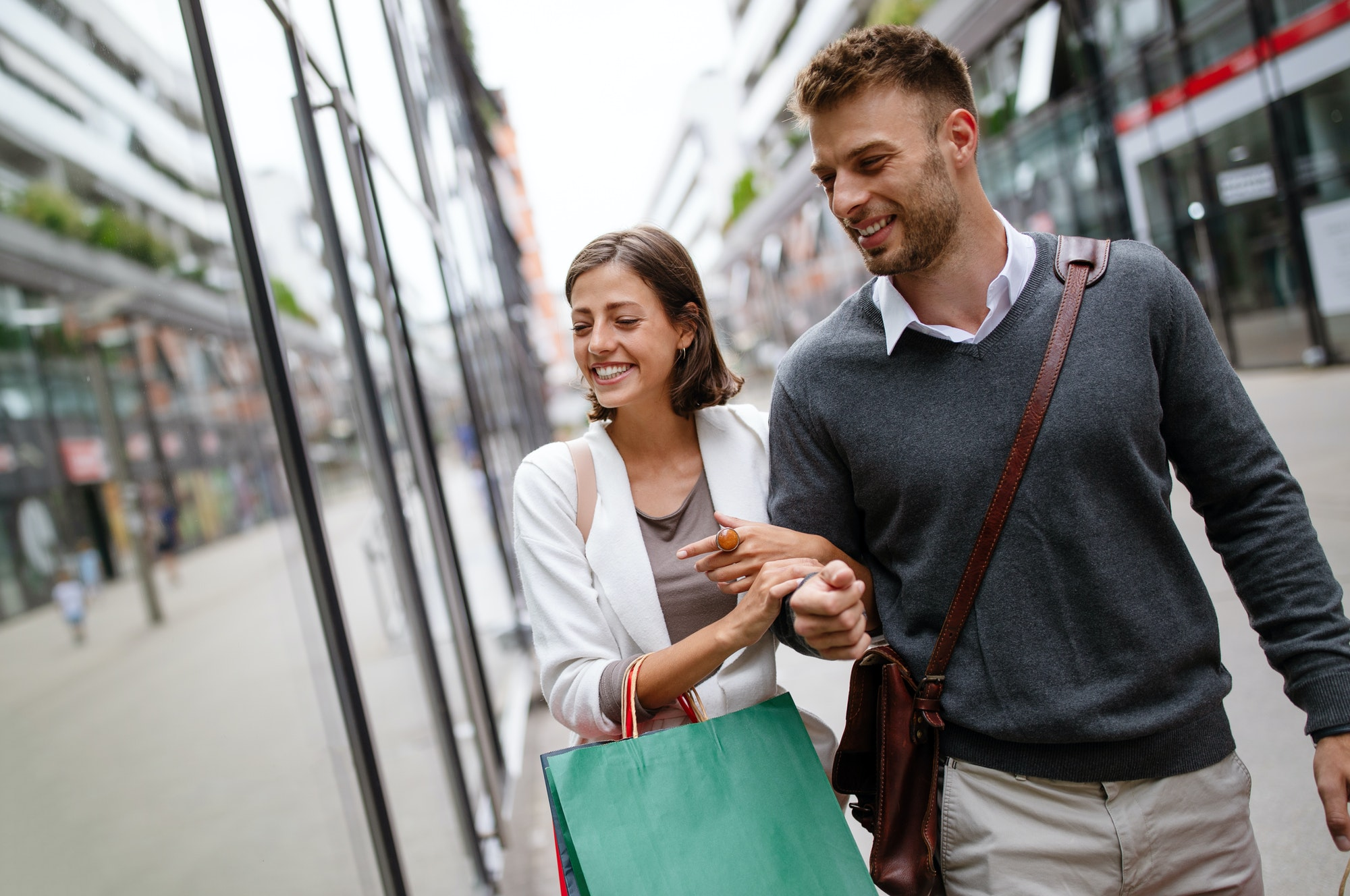 Happy couple with shopping bags. Sale, travel, love consumerism and people concept
